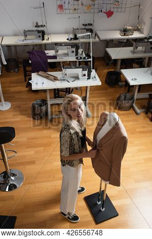 High Angle View Of Fashion Designer Near Mannequin And Sewing Machines In Atelier