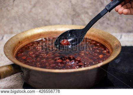 A Mans Hand Holds A Large Spoon With Strawberry Jam On The Background Of Strawberry Jam Cooked In A