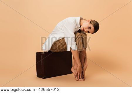 Barefoot Woman In Shirt And Trousers Touching Legs While Sitting On Retro Suitcase On Beige Backgrou