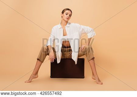 Stylish Barefoot Woman In Trousers And White Shirt Posing On Vintage Suitcase On Beige Background