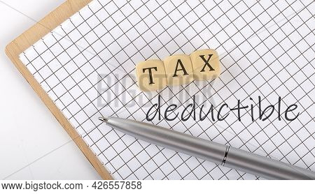 Tax Deductible Text Concept Written On The Wooden Cubes Blocks And Notebook
