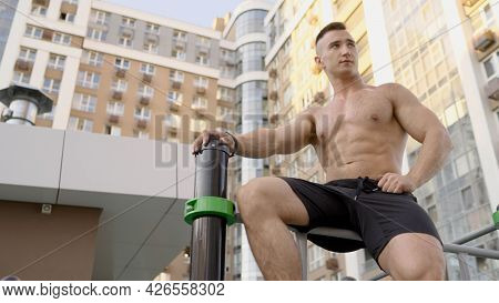 A Strong Man Sits And Rests From Sports. An Athlete With A Naked Torso Sits On A Horizontal Bar Agai