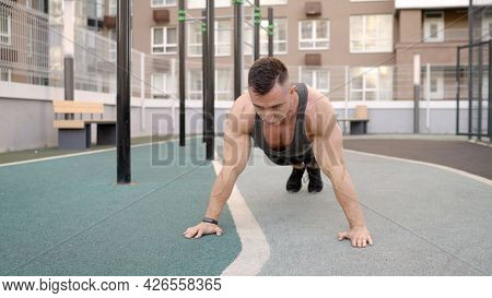 Build Muscles In The Fresh Air. Sport And Healthy Lifestyle Concept. The Guy Does Push-ups On The St