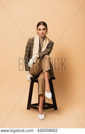 Elegant Woman In Trousers, Blazer, White Shoes And Gloves Sitting On Beige Background
