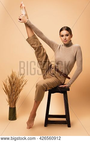 Barefoot Woman In Turtleneck And Trousers Posing On Stool With Raised Leg On Beige Background