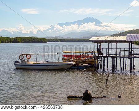 Wooden Jetty With Fishing Boat Moored At Mengkabong River,tuaran Sabah,malaysia.the River An Estuari