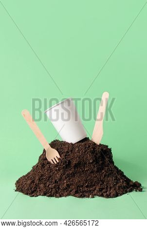 Paper Cup And Wooden Fork, Knife In Heap Of Soil On Green, Vertical With Copy Space. Compostable Or