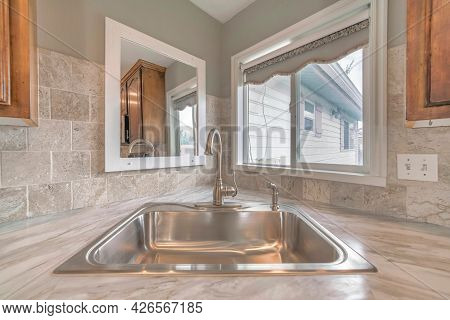 Stainless Steel Sink And Curved Faucet At The Corner Of The Kitchen Countertop