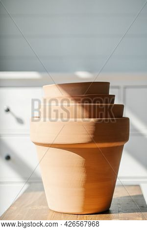 A Stack Of Terracotta Pots On The Background Of The Interior.