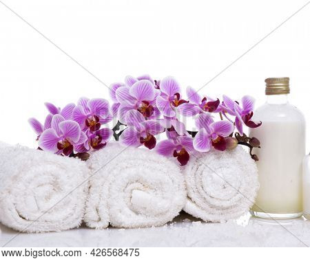 Skin care SPA concept with orchid and rolled towel, oil bottle, ,on white background