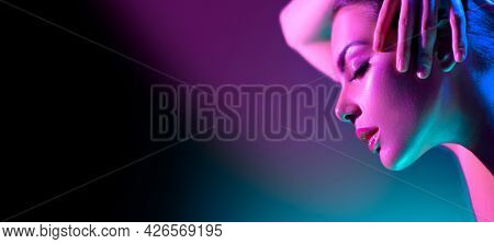 High Fashion model woman in colorful bright neon lights posing in studio, night club. Portrait of beautiful girl in UV. Art design colorful make up. On colourful vivid background, art design