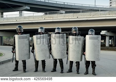 Group of police guards in helmets holding side handle batons and riot shields and standing in row under bridges