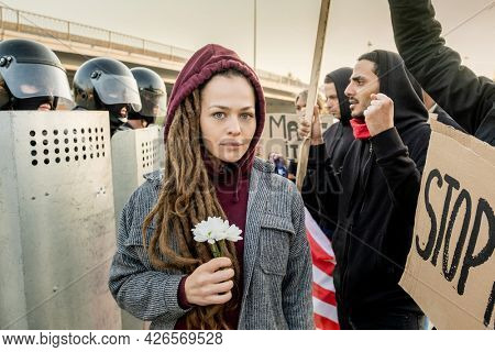 Portrait of scared young Caucasian woman with dreads standing with daisies between police forces and protestors at rally