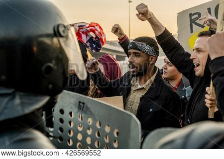 Group of disgruntled young multi-ethnic people raising arms and screaming protecting speech at riot while standing against police with shields