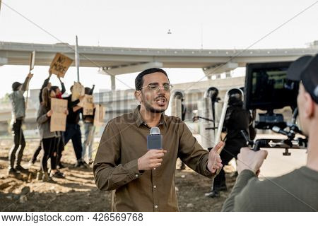 Young mixed race reporter with beard using microphone while covering riot in city: riot police keeping crowd of protestors
