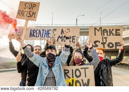 Group of angry young multi-ethnic rebellion people moving with cardboard signs under bridges and fighting for equal rights for all races