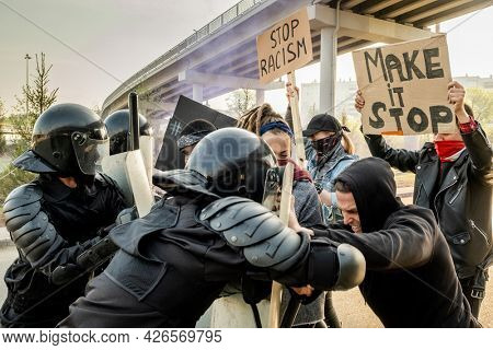 Riot police in helmets pushing protestors with shields while fighting against them at rally