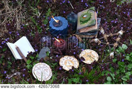 Magic Ritual With Pentagram, Witch Decorated Book Of Spells And Burning Candles Outside. Esoteric, G