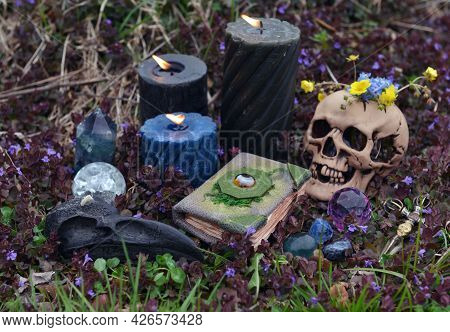 Still Life With Beltane Ritual Objects, Skull, Burning Candles, Crystals And Magic Book Of Spells. E
