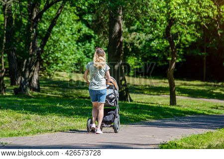 Mother Wheeling A Pram In The Park