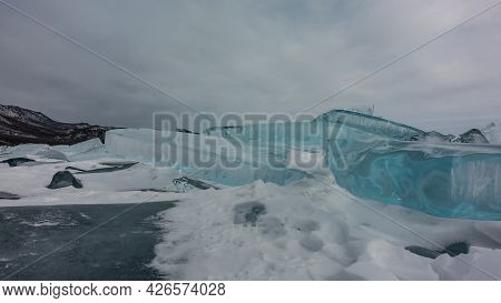A Block Of Ice Hummocks. Close-up. Thick Shiny Turquoise Ice Floes And White Snow On The Surface Of