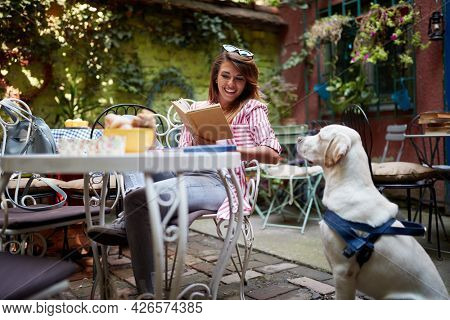 A young beautiful female student is enjoying a company of her dog while reading a book in a pleasant atmosphere in the bar. Leisure, bar, friendship, outdoor