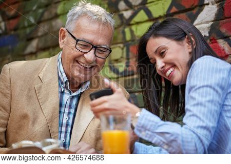 A young beautiful girl is showing a smartphone content to her grandpa while they have a drink in a pleasant atmosphere in the bar. Leisure, bar, friendship, outdoor