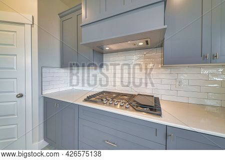 Cooktop Stove Fixed On Kitchen Countertop With Exhaust Hood And Gray Cabinets