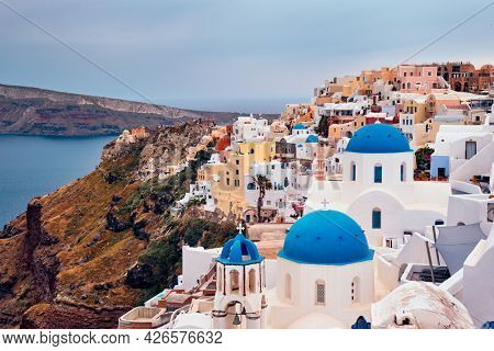 Famous greek iconic selfie spot tourist destination Oia village with traditional white houses and church in Santorini island on sunset in twilight, Greece