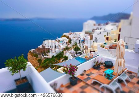 Famous greek iconic selfie spot tourist destination Oia village with traditional white houses and windmills in Santorini island, Greece. Toy camera tilt shift miniature effect