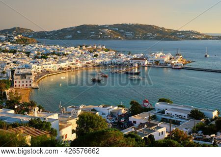 View of Mykonos town Greek tourist holiday vacation destination with famous windmills, and port with boats and yachtson sunset . Mykonos, Cyclades islands, Greece.