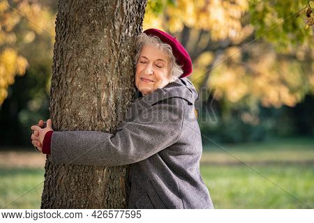 Beautiful senior woman hugging tree in the park. Mature woman hugging a tree and smiling outdoor. Senior lady with grey hair wearing red cap and coat embracing a trunk with eyes closed during autumn.