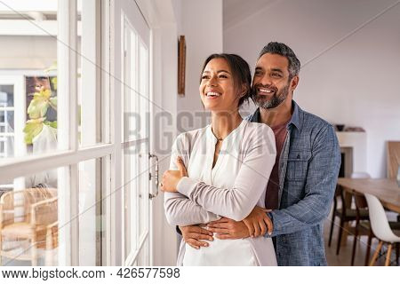 Smiling mid adult couple hugging each other and standing near window while looking outside. Happy and romantic mature man embracing hispanic wife from behind while standing at home with copy space.
