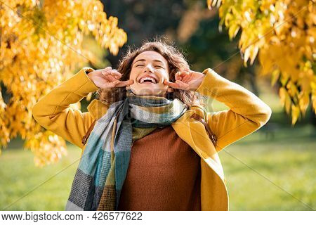 Carefree natural beauty woman enjoying freedom with yellow leaves on trees in background. Playful girl wearing coat and scarf laughing during autumn outdoor. Beautiful girl using finger while laughing