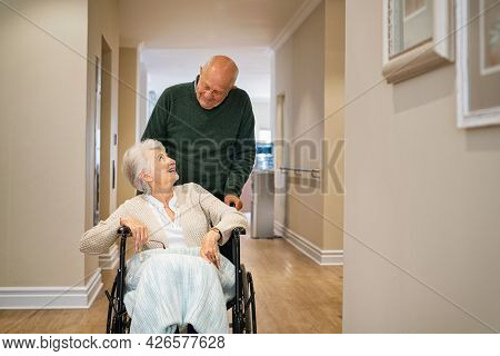 Old man pushing disabled wife on wheelchair in hospital hallway. Happy smiling senior woman in a wheelchair relaxing with her husband in care centre during a visit. Elderly man pushing his old wife.