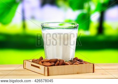 Almond Milk With Almond Kernels. Alternative Milk For Vegetarians. Milk In A Glass On A Green Natura