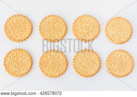 Round Cookie White Background Top View. Eight Light Yellow Crackers Lie In Two Rows. A Food Texture