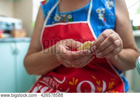 A Woman In The Kitchen Prepares Dumplings From Dough And Minced Meat