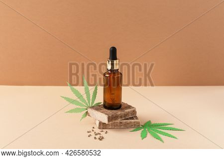 Cannabis Oil Extract In Droplet Bottle On Brown Background. Medical Marijuana Cbd Oil. Alternative M