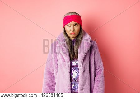Sad And Indecisive Asian Senior Woman In Fashionable Faux Fur Coat Looking Left And Sulking Upset, S