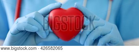 Doctor In Gloves Holds A Red Heart Closeup