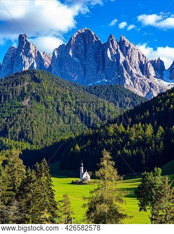 Charming old little church in the Val de Funes. Magnificent Dolomites on a sunny autumn day. Green meadows in the Val de Funes. Europe, Italy, Tirol
