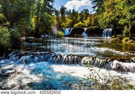 Dense forests surround the city and the river. The small Croatian town of Slunj. Magnificent cascade of waterfalls on the Korana River. The concept of ecological, active and photo tourism