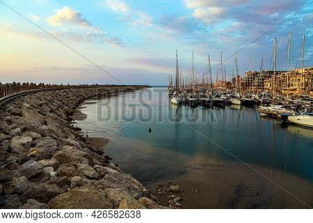 Marina is harbor for yachts, boats and small boats in Herzliya, Israel. Evening twilight on the Mediterranean Sea. Walk along the breakwater that protects the yacht harbor from storms