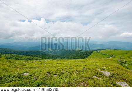 Green Nature Landscape. Beautiful Summer Scenery In Mountains. Stones On The Grassy Hills Rolling In