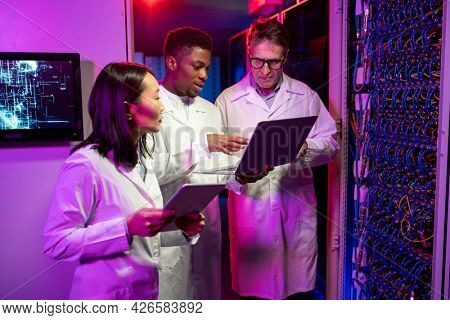 Group of multi-ethnic network server technicians in lab coats standing at server cabinet and using devices while discussing internet connection