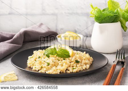 Boiled Bulgur With Fresh Lemon And Mint On A Plate. A Traditional Oriental Dish Called Tabouleh. Gra