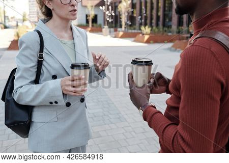 Elegant male and female co-workers with drinks interacting in the street