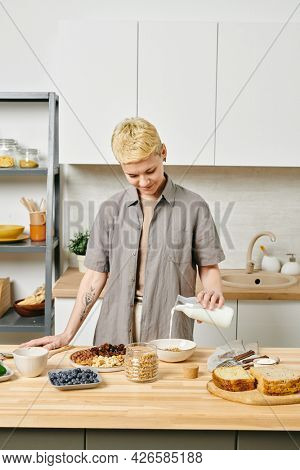 Young woman pouring fresh milk into bowl with muesli by kitchen table