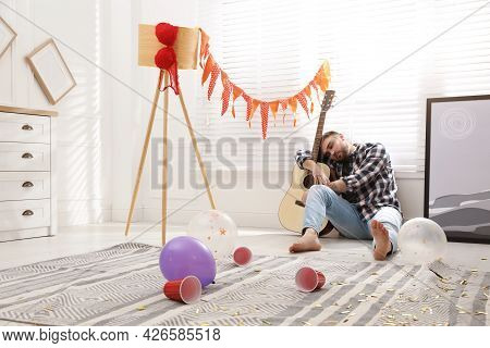Young Man With Guitar Sleeping Near Window In Messy Room After Party